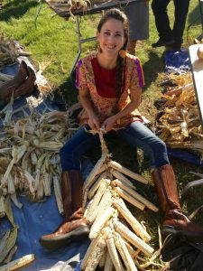 Woman sits on the ground husking corn
