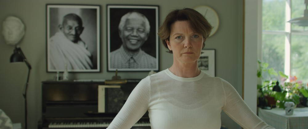 A middle-aged woman in a white long sleeve shirt stares sternly at the camera in front of photo portraits of Mahatma Gandhi and Nelson Mandela.