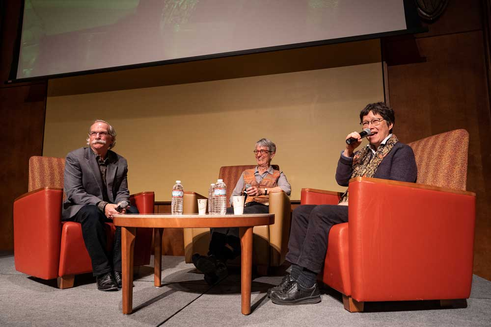Gregg Mitman, Donna Haraway, and Anna Tsing sit in chairs on stage during the Plantationocene seminar, as Tsing speaks into a microphone.