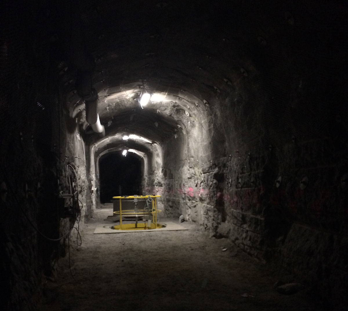 A dark concrete tunnel with yellow equipment.