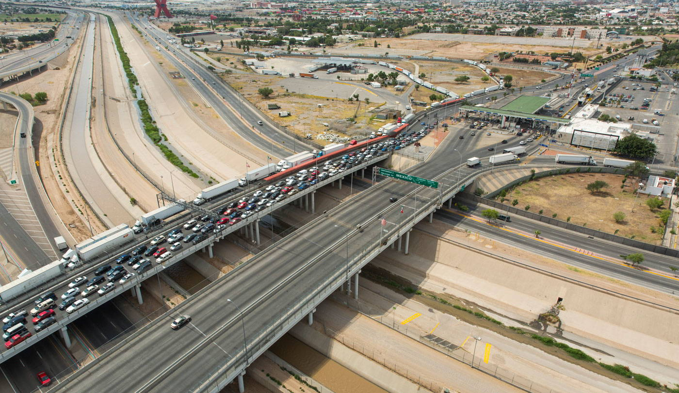 a bridge crowded with cars stretches over a mostly dry riverbed of concrete