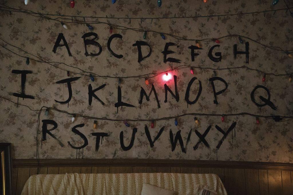 Alphabet written over floral wallpaper.