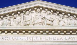 """The facade of the U.S. Supreme Court building, with the phrase """"equal justice under law"""" carved into white stone"""