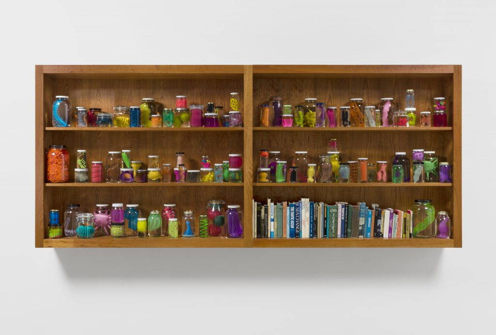 A wooden bookcase with jars of colorful plastic objects on the shelves
