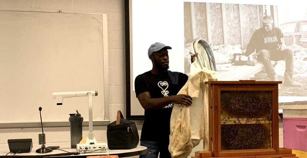 Kamal Bell stands next to a box of bees in a classroom, demonstrating beekeeping techniques.