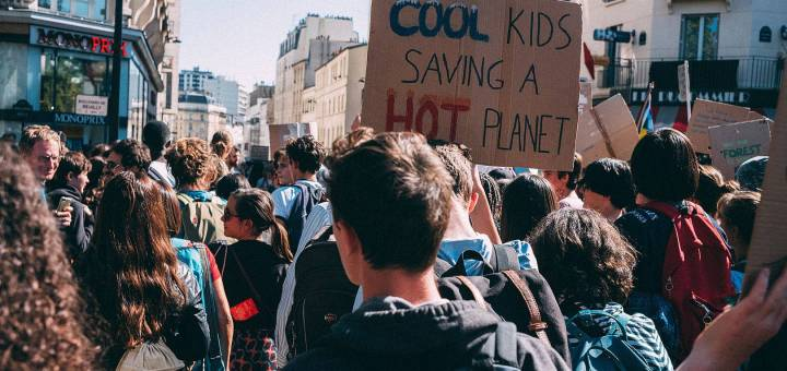 """A group of protestors in Paris, one holding a sign that reads """"cool kids saving a hot planet"""""""