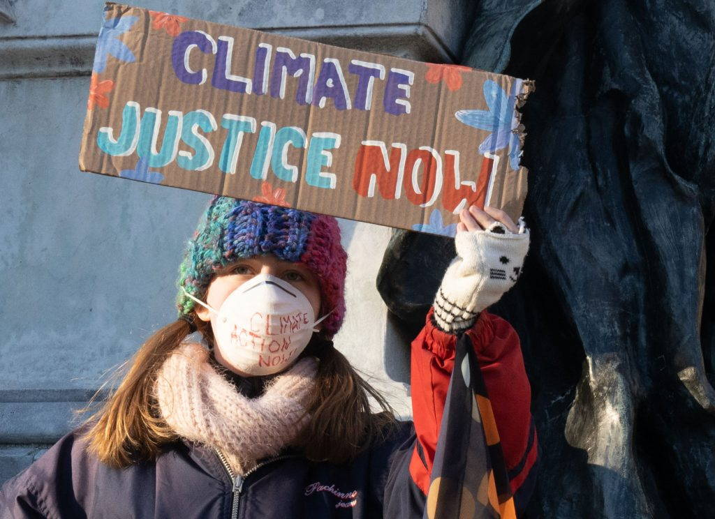 """A young person wears a face mask and holds a sign reading """"climate justice now"""""""