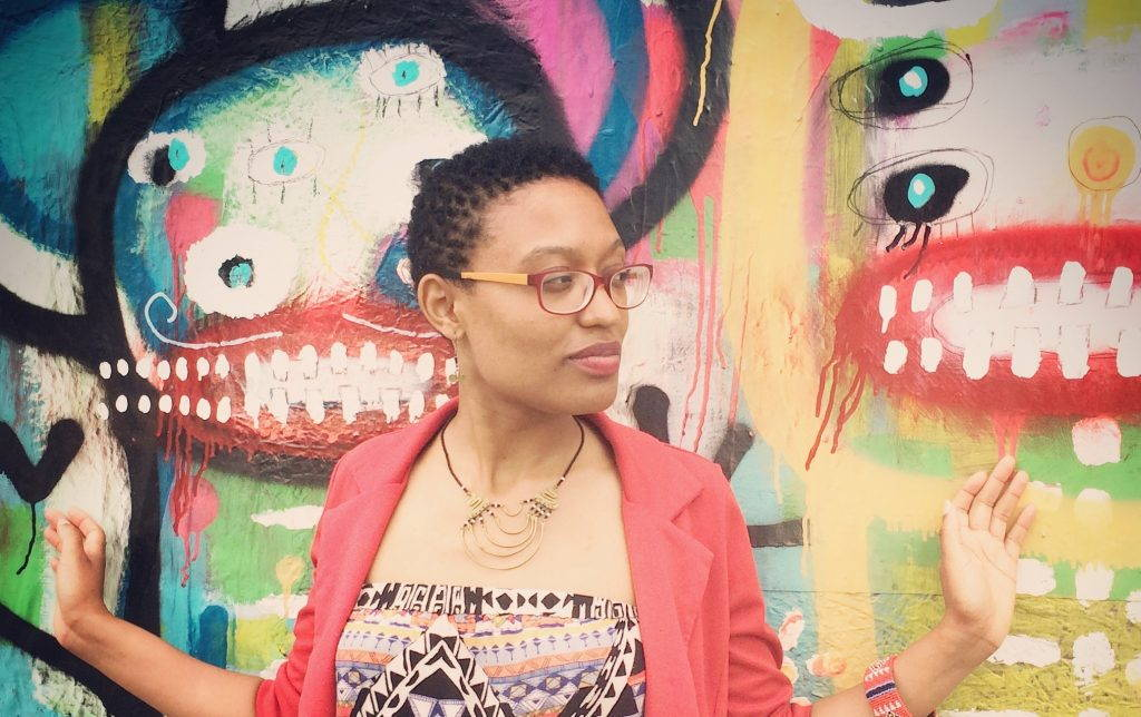 Woman wearing glasses poses in front of colorful mural.