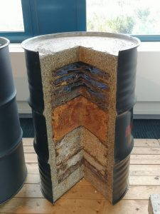 Barrel that has been vertically cut open to reveal multiple layers of nuclear waste.