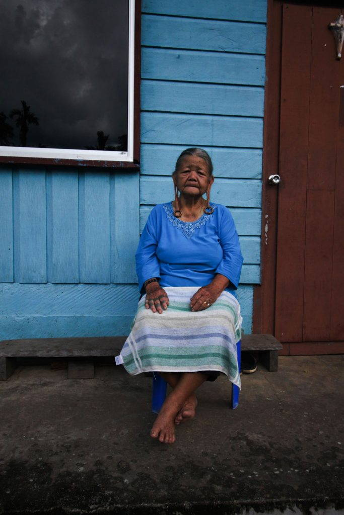 Old woman sitting in front of a blue wall