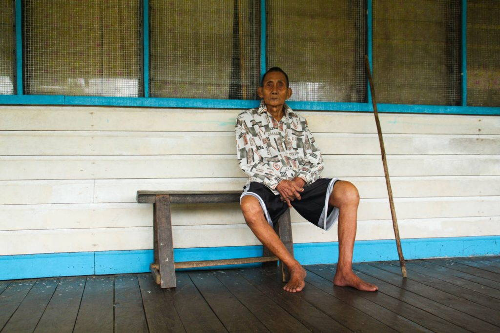 Old man sitting on the longhouse veranda with his walking stick