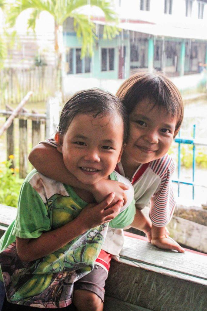 Two children smiling on the veranda