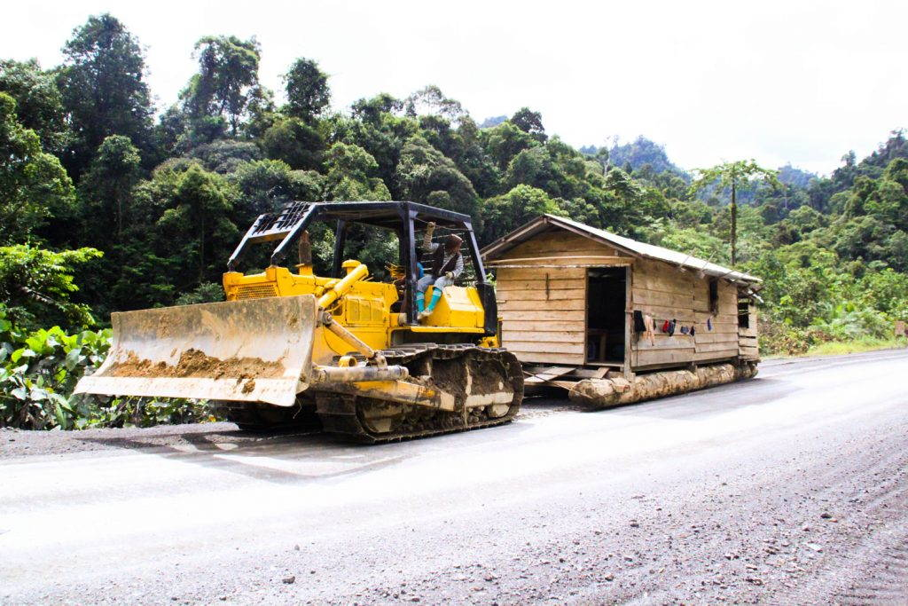 House being towed by a bulldozer along road