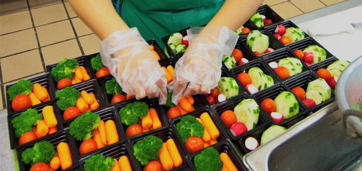 Close-up on gloved hands filling vegetable cups with carrots, tomato, and broccoli.