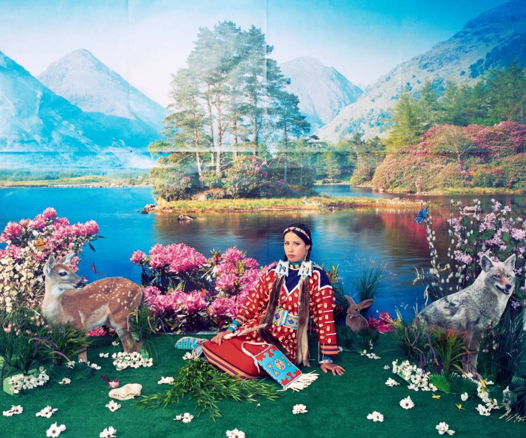 Woman sits on green grass between a deer and a wolf. Lake and mountains in background.