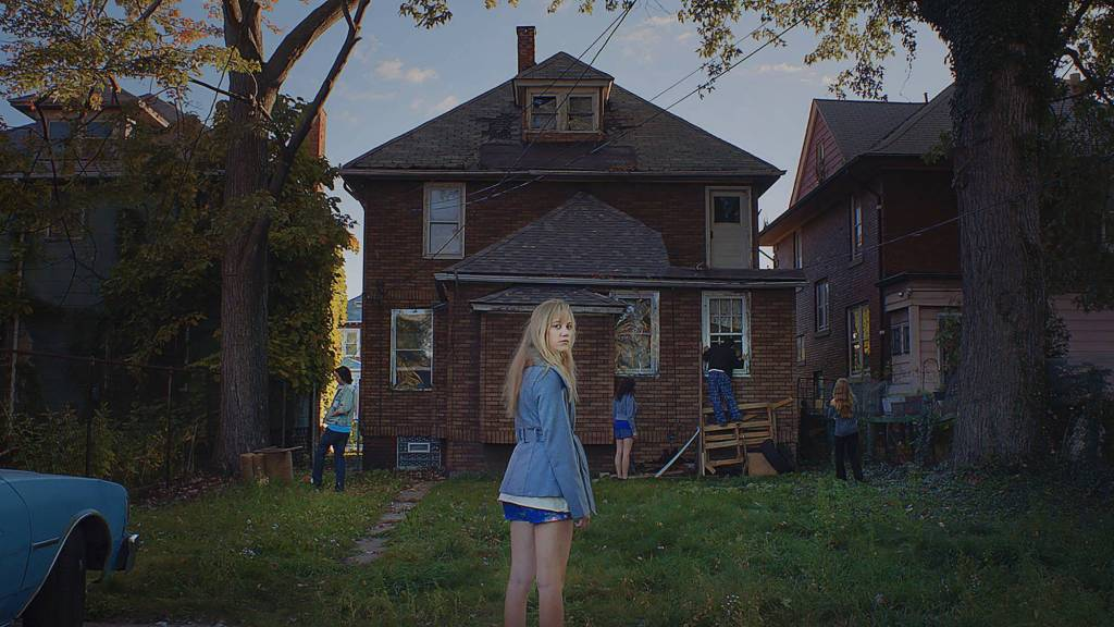 A teenage girls stands in front of an old house with broken and boarded windows.
