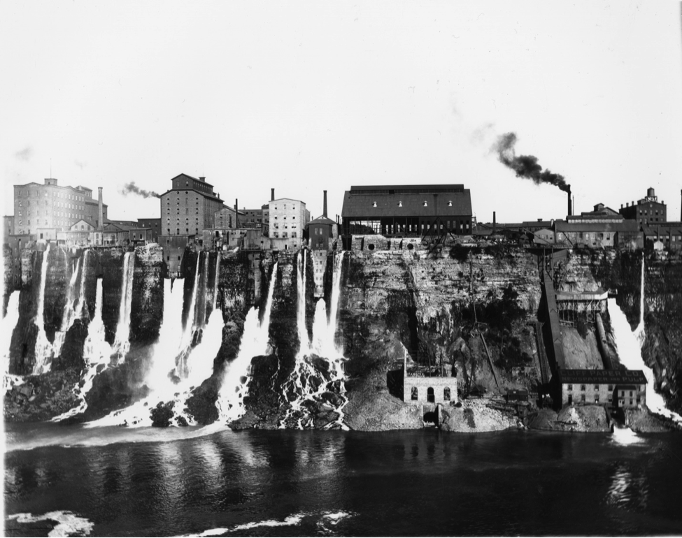 A row of industrial buildings with water flowing from outtake pipes down a cliff into a river