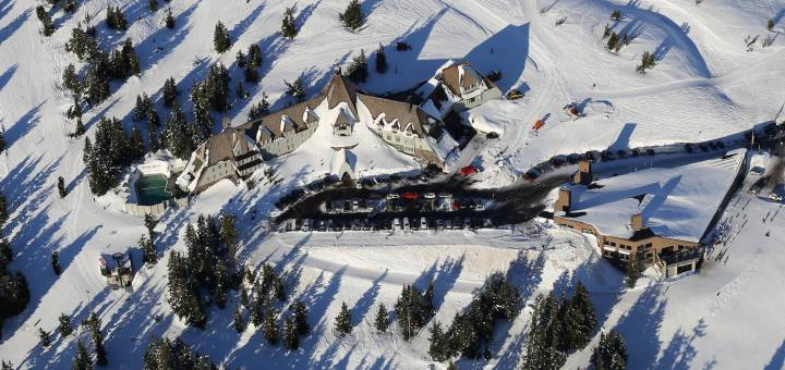 Timberline lodge surrounded by snow with parked cars and ski tracks.