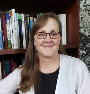 A woman with brunette hair and glasses in front of a bookshelf. Headshot of Gail Carlson.