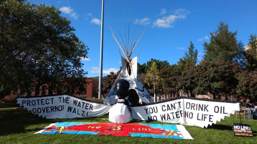 """Elaborate protest display in park reads """"Protect the water, Governor Walz! You can't drink oil. No water, no life."""""""