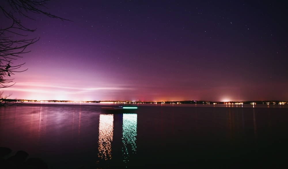 A boat floats across Lake Mendota in front of the city at night.