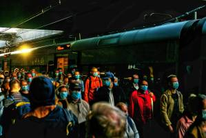 a crowd of people wearing mask on platform at a train station