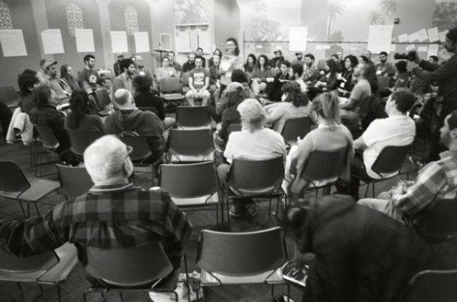 An audience of people sitting in a circle around a speaker in the center