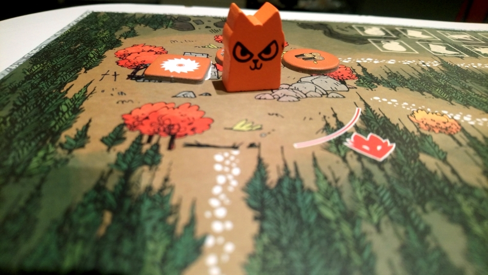 An orange cat piece sits on a brown game board.