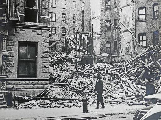A black man walks in front of a destroyed house.