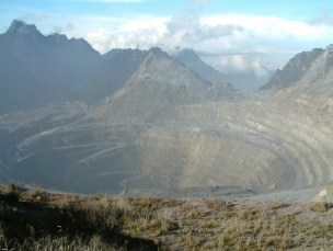 Open pit mine in the mountains with clouds and blue sky