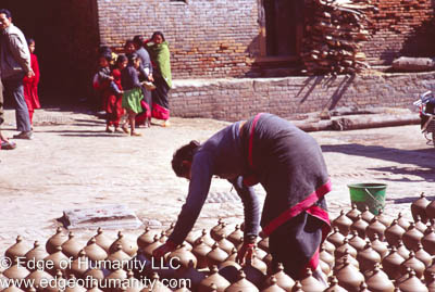 Nepal - Bkaktapur: Woman placing pottery jars in the Town Square to dry.