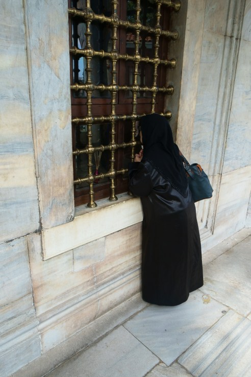 Süleymaniye Camii - an elderly lady peers through the window at the tomb of Süleyman the Magnificent.