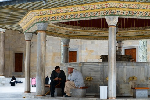 Fatih Camii - two men linger to talk after Friday prayer, at the 'Mosque of the Conqueror while the women wait in the courtyard.