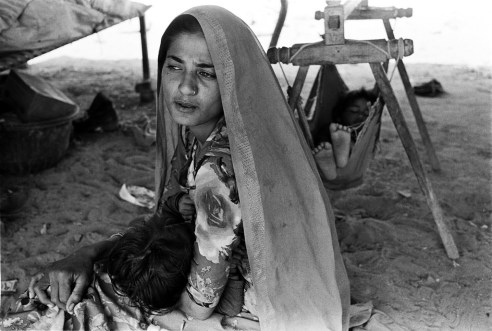 Gypsy woman is sitting with a child in her hands with another baby in the crib in the background Rural Rajasthan, India