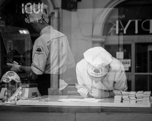 Chocolate Girl, Krakow, Poland Passing by an artisan chocolate shop in Krakow I saw this young lady concentrating on icing small slabs of white chocolate.