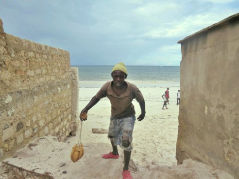 A Diani Beach worker goes home at twilight, having failed to sell his bird feeder carved from a single coconut.
