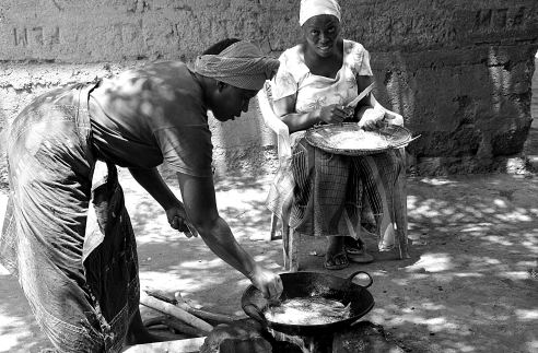 """""""Frying Fish"""" This shot was taken in Moshi, Tanzania the day before my hike up Kilimanjaro. I was exploring the town out in the rural settlements. These two ladies are preparing traditional cooked fish which is hung up to dry."""