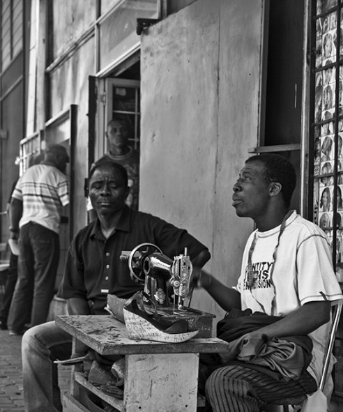 """""""The tailor on main"""" This shot is of a man doing tailor work on main road, New Town, Johannesburg. I just loved the way the streets are alive with culture and vibe. This man is putting his trade to direct use to the public right on the road. Hats off to him"""