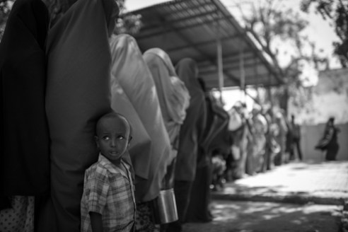 Refugees are lined in preparation for a hot meal of beans and rice provided by the Turkish Red Crescent Society. Hamar Weyne district, Mogadishu, Somalia.
