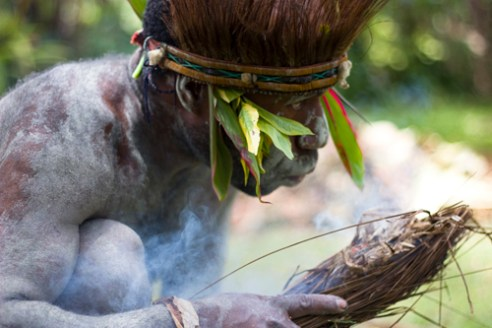 The ritual begins with the lighting of a fire to welcome the arrival of masked warriors. Asaro Mudmen Tribe - Goroka, Central HIghlands, PNG