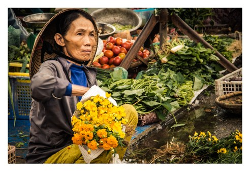 A Woman sells flowers in a street stall in Hoi An, Vietnam.