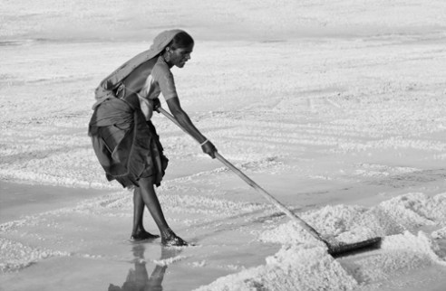 Sandhi Woman working in salt pans in searing heat. Their feet are exposed to salt water over prolonged periods. When cremated their ankles do not disintegrate like rest of the body.