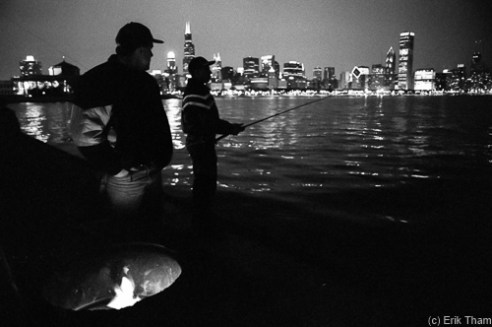 Chicago, IL: Two fishermen during night fishing at Navy Pier at the waterfront of Lake Michigan in front of Chicago's illuminated skyline in the background.