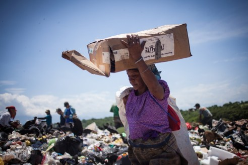 A woman in a colourful dress typical for the indigenous community most of the migrants from Guatemala that work at the rubbish dump belong to, is carrying recycled paper on her head. During their work, the women and men are exposed not only to bad smell and toxic materials that, according to local activists, are unloaded by corporations at the rubbish dump, but also to the direct impact of sunlight at temperatures that can reach 40 degree Celsius.