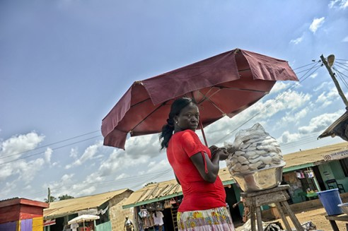 The lady in red along the road between Accra in Ghana and Lomé in Togo through almost every village you drive vendors line the road with local specialties delicacies and refreshments here it seems to be freshly hacked coconut. Ghana