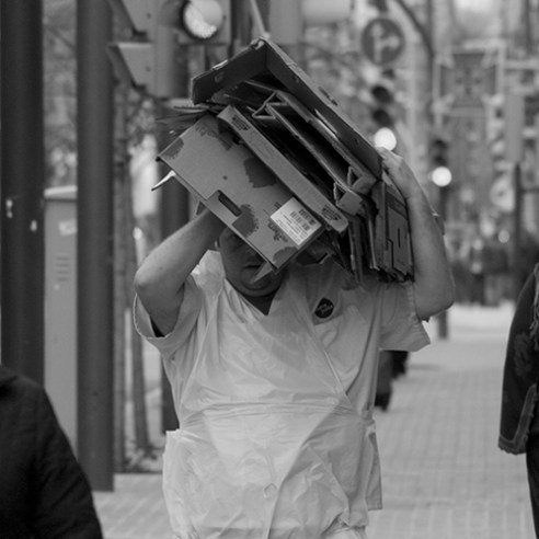 Man carrying cardboards in Collblanc Road in L'Hospitalet de LLobregat.
