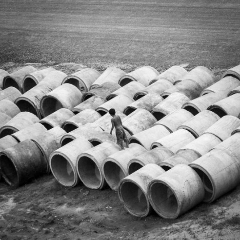 Kid on cement tubes Cambodia