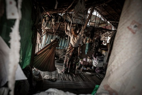 Mae Sot, Thailand; February 2014. An elderly woman cradling a child inside a hut.
