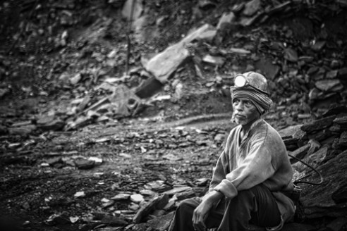 """Miner"" resting after many hours of digging coal underground."