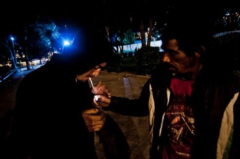 Vendedores ambulantes nocturnos de la Plaza O'higgins consumen pasta base, una de las drogas mas destructivas y dependientes del mercado. Valparaíso. Night hawkers doing drugs at The Plaza O'Higgins, Valparaiso, Chile